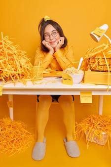 Un étudiant asiatique rêveur est assis au bureau, rêve de vacances, garde les mains sous le menton, aime l'atmosphère domestique, habillé avec désinvolture, fait des notes de service se prépare pour un test ou un examen isolé sur un mur jaune