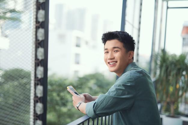 Étudiant asiatique textos sur smartphone au balcon