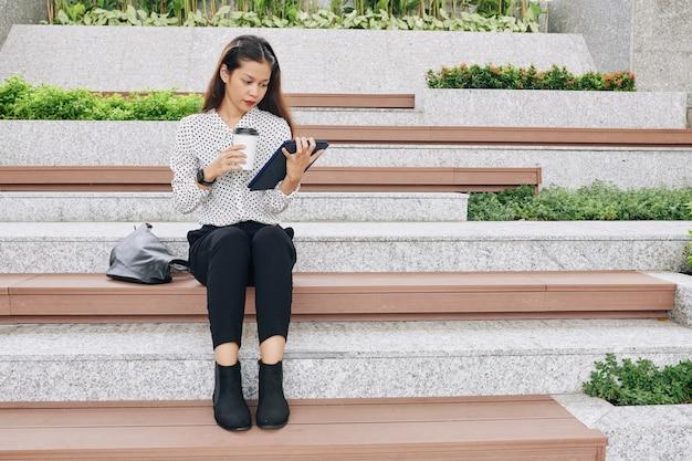 Étudiant assis sur un banc sur le campus avec tasse de café à emporter et lecture de livre électronique