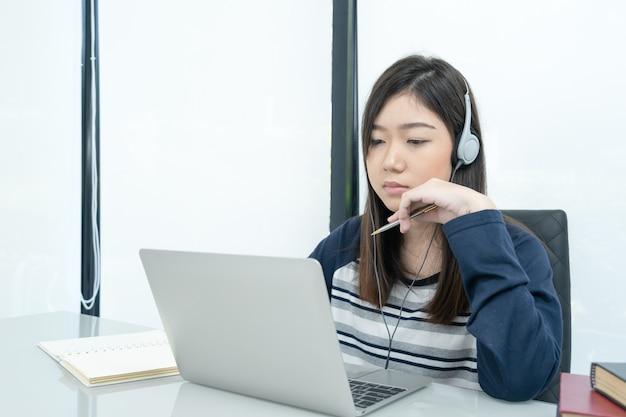 Étudiant assis dans le salon et apprenant en ligne