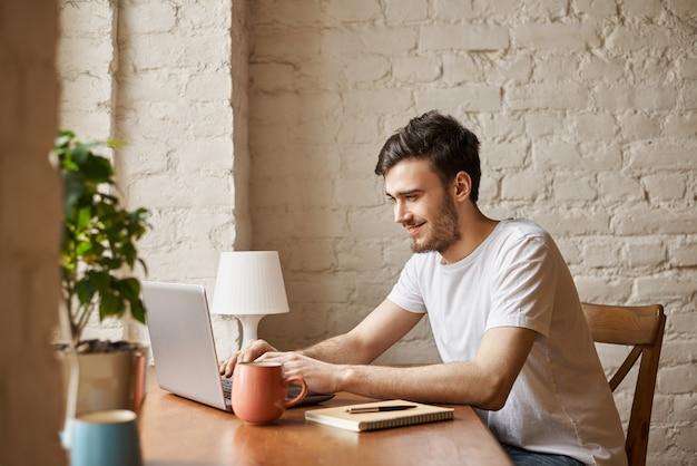 Un étudiant attrayant utilise la technologie internet et une connexion wi-fi haut débit pour discuter avec un ami
