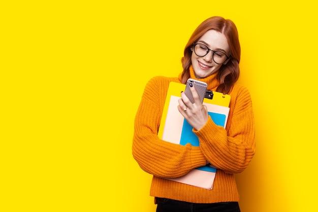 Étudiant au gingembre aux taches de rousseur utilisant un téléphone sur fond jaune concept éducatif de chat sms