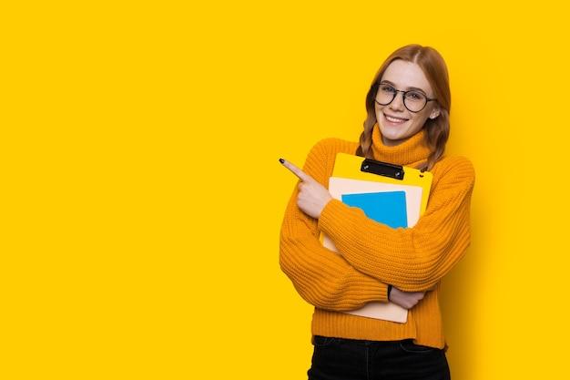 Étudiant au gingembre avec des taches de rousseur et des lunettes pointant vers l'espace libre jaune près d'elle avec le doigt embrassant des livres