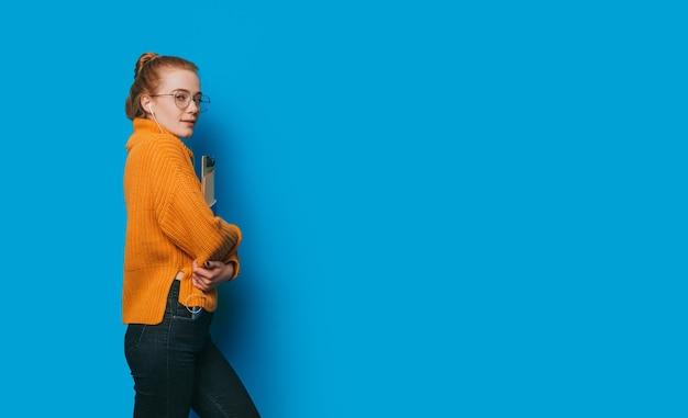 Un étudiant aux cheveux roux qui travaille dur fait la promotion de certains articles universitaires posant près du grand espace vide