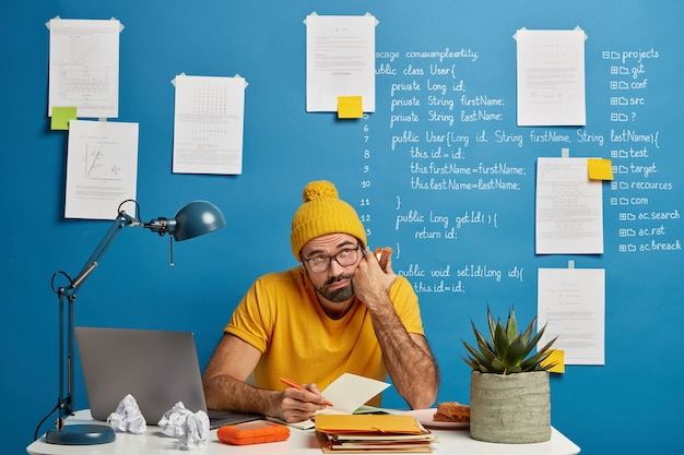 Un étudiant barbu contemplatif prend des notes dans le bloc-notes pendant le travail à distance avec un ordinateur portable, mange un délicieux sandwich, écrit des idées pour créer son propre site web