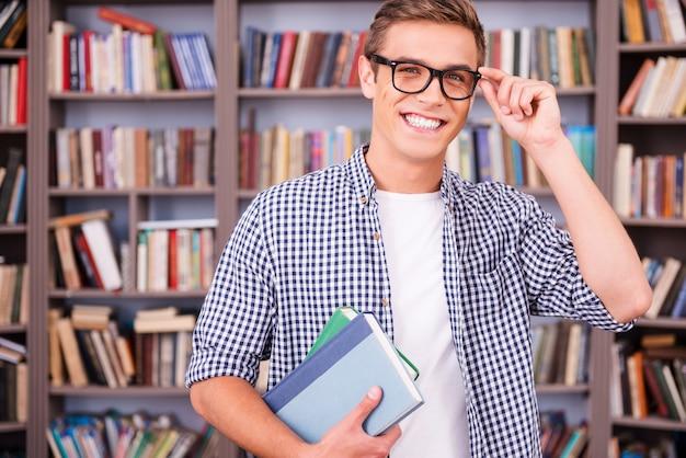 Étudiant en bibliothèque. beau jeune homme tenant des livres et souriant en se tenant debout dans la bibliothèque