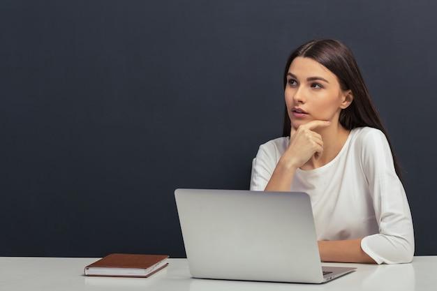Étudiant en blouse blanche garde la main sur le menton.