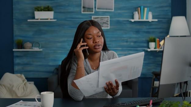 Étudiant bouleversé assis à une table de bureau dans le salon expliquant les devoirs du lycée discutant avec un collègue à l'aide d'un smartphone