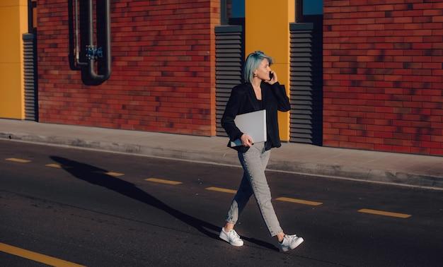 Étudiant caucasien aux cheveux bleus marchant dans la rue tout en ayant une discussion téléphonique et tenant un ordinateur portable