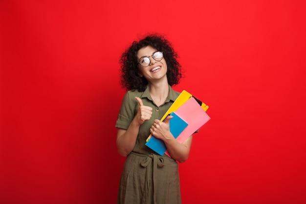 Étudiant caucasien aux cheveux bouclés tient des livres et fait des gestes le signe similaire tout en posant sur un mur rouge