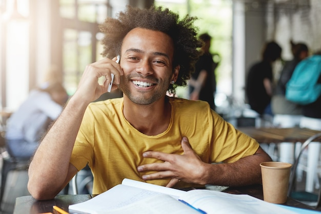 Étudiant avec une coiffure touffue ayant une conversation agréable sur téléphone portable