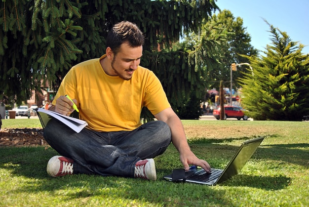 Étudiant collégial allongé sur l'herbe au soleil avec un ordinateur