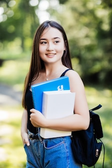 Étudiant détenant des livres marchant sur le campus va en classe en souriant. jeune fille souriante femme asiatique multiraciale avec sac portrait en plein air.