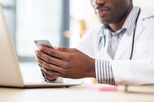 Étudiant détendu portant un uniforme médical et jouant avec le téléphone en pause