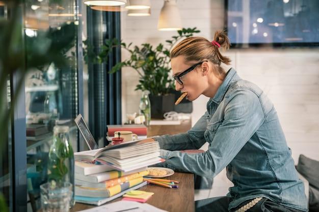 Étudiant diligent. homme sérieux intelligent travaillant sur l'ordinateur portable tout en mangeant une collation