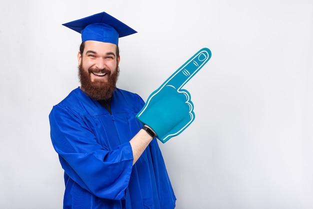 Un étudiant diplômé excité crie et porte un gant de fan pointant sur le fond.