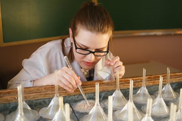Étudiant diplômé femme analize graines sur table de germination.