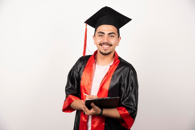 Étudiant diplômé positif avec diplôme regardant la caméra sur blanc.