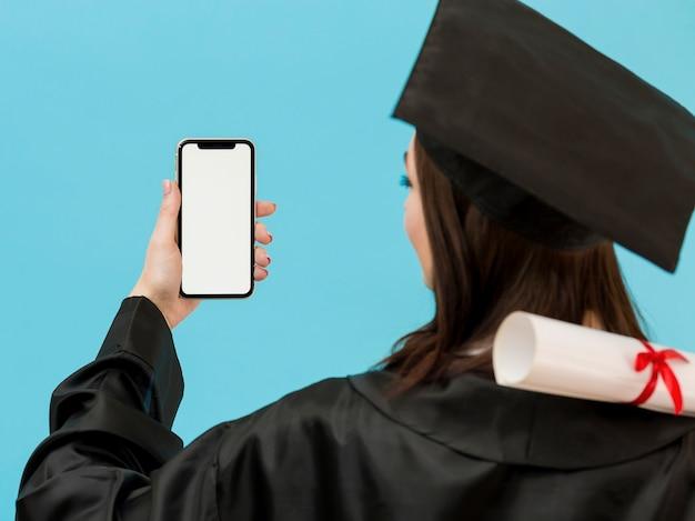 Étudiant diplômé avec smartphone