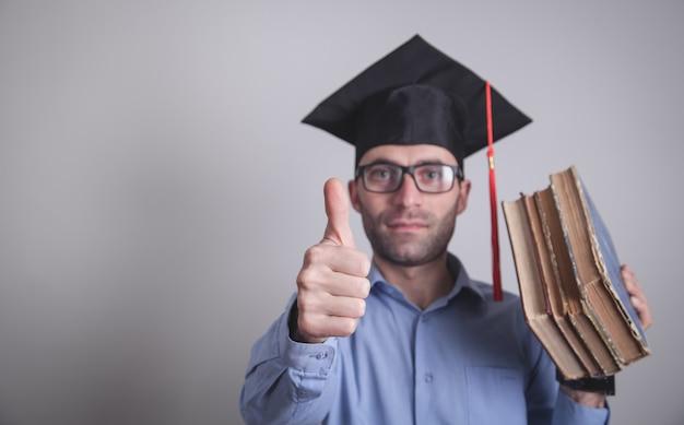 Étudiant diplômé tenant des livres au bureau.