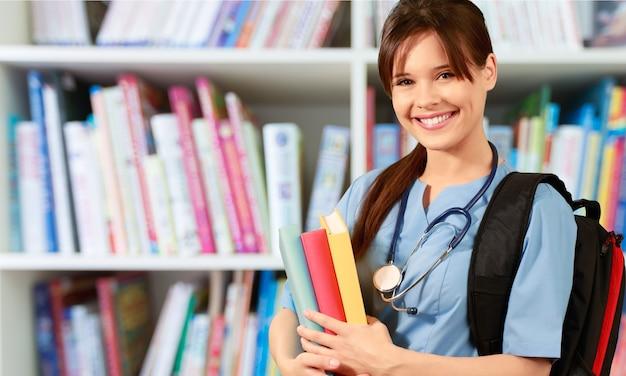 Étudiant de l'école de médecine avec sac à dos tenant des livres
