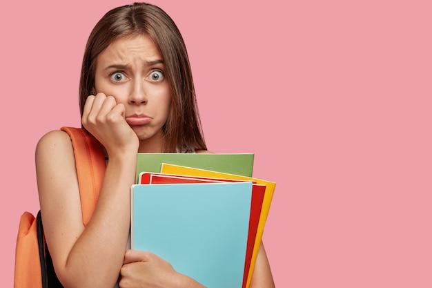 Étudiant effrayé posant contre le mur rose