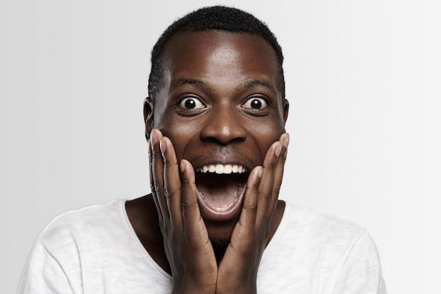 Étudiant ou employé africain choqué en pleine incrédulité, les mains sur les joues, la bouche grande ouverte, surpris par des nouvelles inattendues ou des prix de vente élevés.