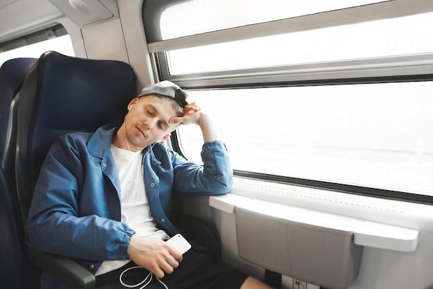 Un étudiant endormi dort dans le train le matin et écoute de la musique au casque.