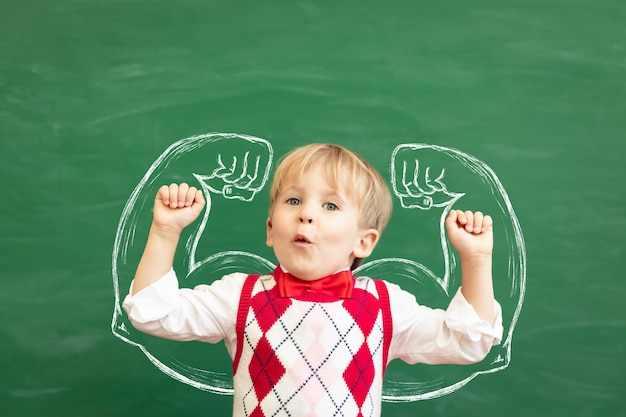 Étudiant enfant drôle en classe contre tableau vert. éducation physique.