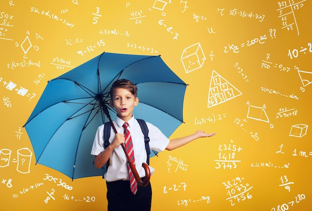 Étudiant enfant avec parapluie bleu se couvrir d'une pluie oa beaucoup d'exercices de mathématiques et d'algèbre