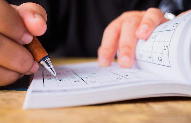 L'étudiant essaie de résoudre sudoku avec un crayon de couleur
