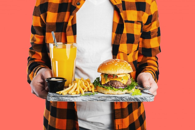 Un étudiant est en train de tenir le tableau avec un burger frais.