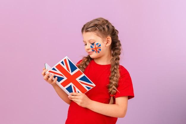 Un étudiant étudie un livre en anglais sur un fond violet isolé. apprendre des langues étrangères.