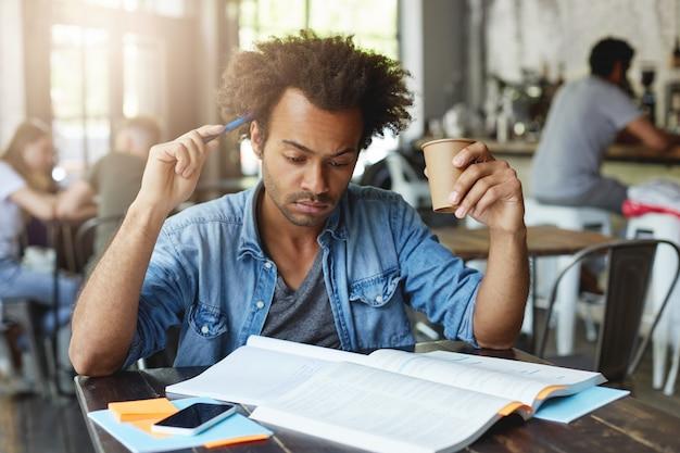 Étudiant européen noir concentré et réfléchi avec une coiffure afro se grattant la tête avec un stylo, buvant du thé chaud au café, se préparant à une leçon de français à l'université, traduisant un article dans un manuel