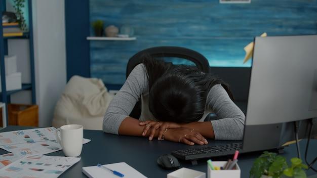 Étudiant fatigué et fatigué dormant sur une table de bureau dans le salon