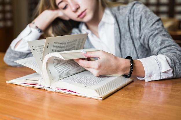 Étudiant fatigué feuilletant des pages de livre