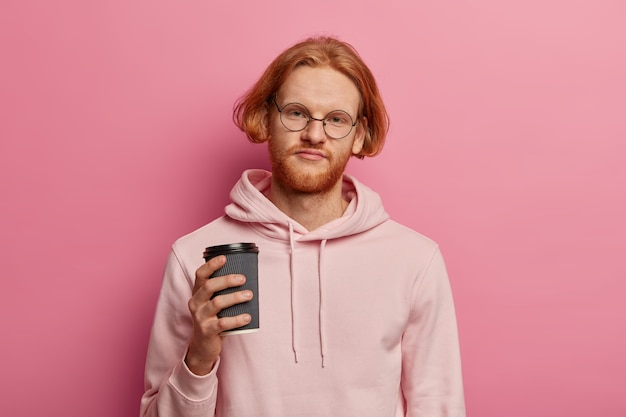 Un étudiant fatigué et mécontent essaie de se rafraîchir avec une tasse de café à emporter, regarde avec une expression contrariée, vêtu d'un sweat à capuche, a besoin d'un bon repos, a des cheveux roux isolés sur un mur rose
