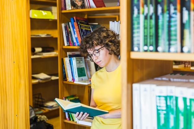 Étudiant femme debout derrière une bibliothèque