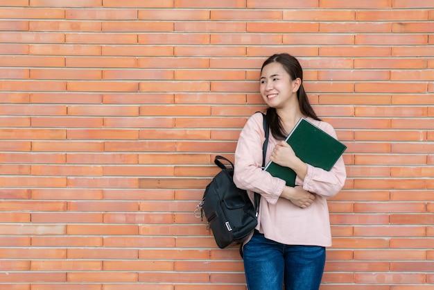 Étudiant femme souriante tenant livre posant sur fond de brique sur le campus.