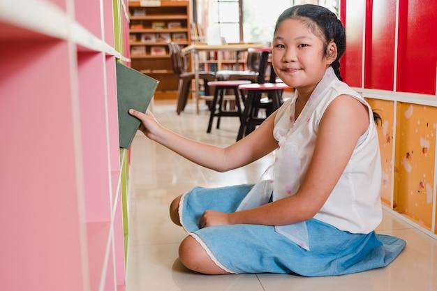 Étudiant de fille adolescente souriante, choisir des livres de la bibliothèque de l'étagère à l'école.