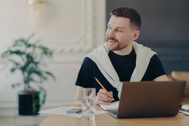 Un étudiant gai recherche des informations pour ses devoirs via un ordinateur portable écrit un article assis dans un espace de coworking tout en détournant les yeux avec un sourire heureux sur le visage regarde un webinaire de formation crée un blog personnel