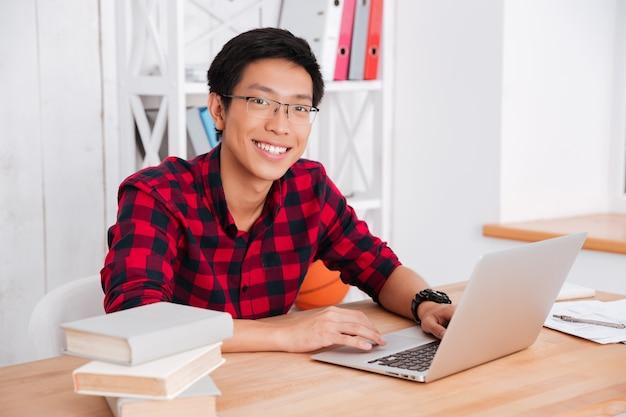 Étudiant gai regardant à l'avant et travaillant sur son ordinateur portable en classe. assis près des livres
