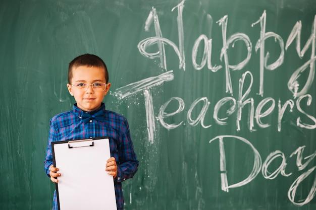 Étudiant garçon debout sur fond de tableau noir le jour des enseignants
