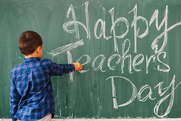 Étudiant garçon écrit sur le tableau noir félicitation à l'enseignant