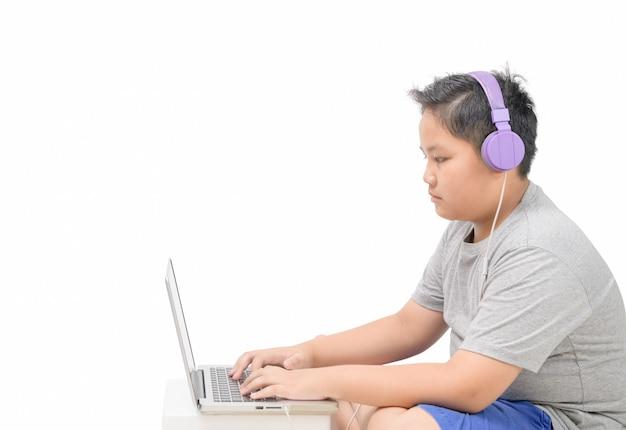 Étudiant garçon obèse porter des écouteurs étudier en ligne avec professeur isolé
