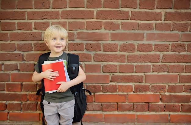 Étudiant avec grand sac à dos près du bâtiment de l'école.