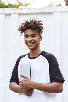 Étudiant heureux homme africain debout à l'extérieur