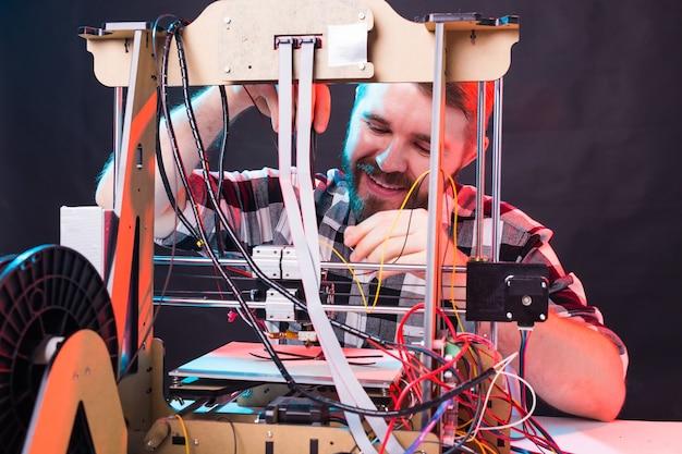 Un étudiant homme imprime un prototype sur une imprimante.