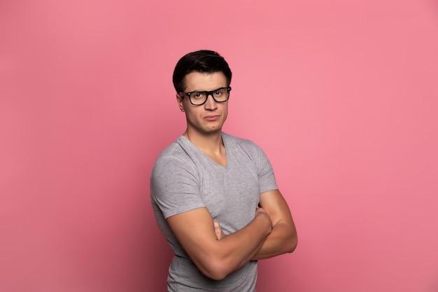 Un étudiant. homme sérieux à lunettes, qui regarde dans la caméra, debout en demi-profil avec les bras croisés.