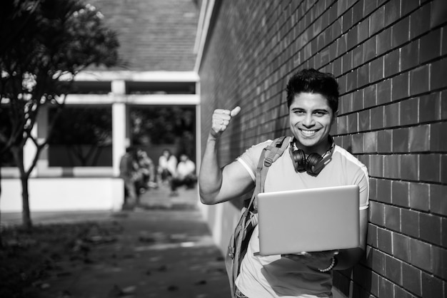 Étudiant indien asiatique concentré travaillant sur un ordinateur portable ou lisant un livre tandis que d'autres camarades de classe en arrière-plan, photo en plein air sur le campus universitaire